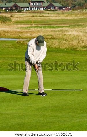 Golfer playing a putt stroke