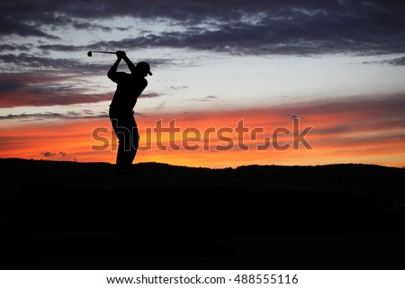 Golfer playing golf during beautiful sunset at competition event