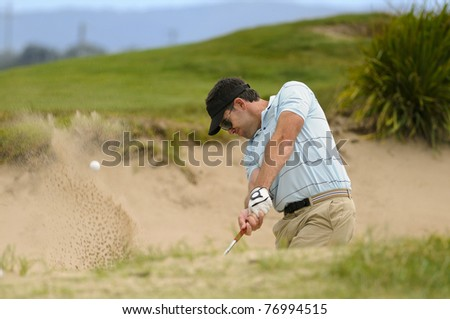 Golfer plays a sand trap shot during his round - stock photo
