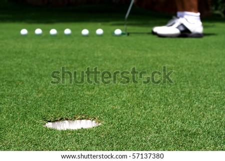 Golfer putting a golf ball - stock photo