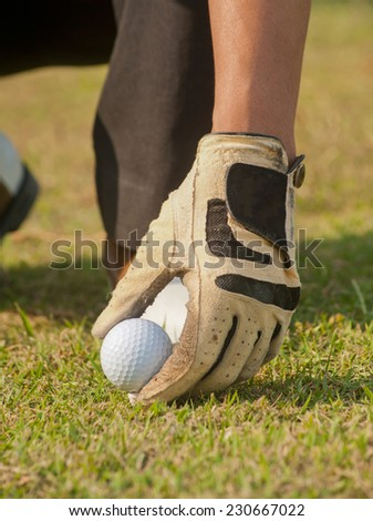 Golfer putting a golf ball on a tee. - stock photo