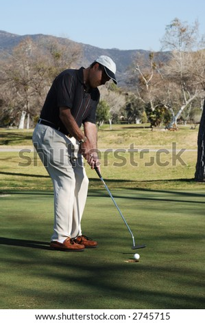 Golfer putting a golfball into the hole on a golf course putting green - stock photo