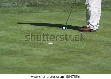 Golfer putting (ball by club) - stock photo