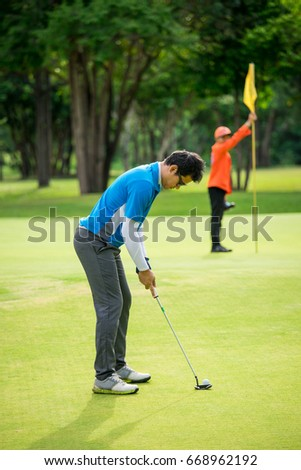 Golfer putting golf-ball to flag hole, blur Caddy holding flag hole on background.