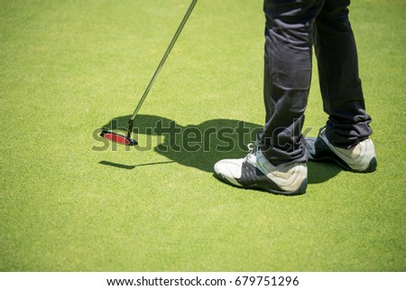 golfer putting golf ball to hole