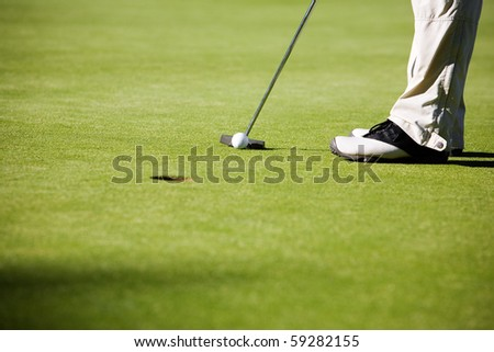 Golfer putting, selective focus on golf ball - stock photo