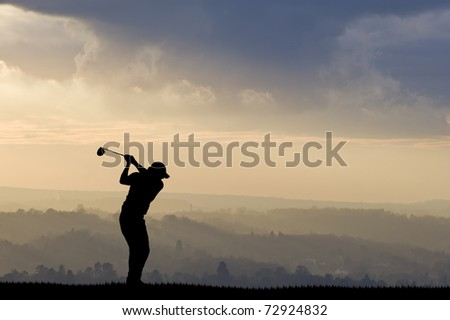 Golfer silhouette against stunning sunset sky - stock photo