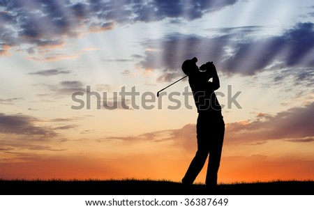 Golfer silhouetted against beautiful sunrise - stock photo