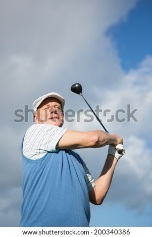 Golfer standing and swinging his club on a sunny day at the golf course - stock photo
