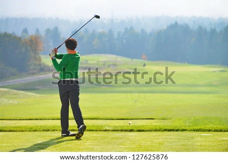 Golfer swing, teeing off on beautiful summer morning - stock photo