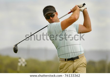 Golfer swings his driver off the tee - stock photo