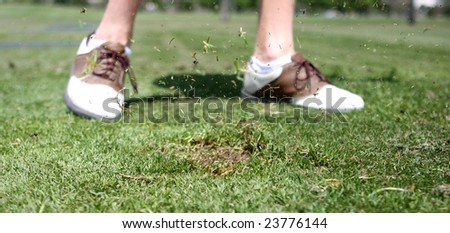 Golfer taking a divot at driving range - stock photo