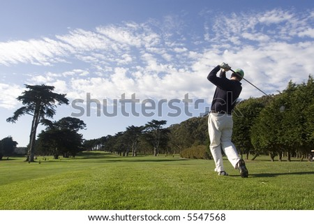 Golfer teeing off - stock photo