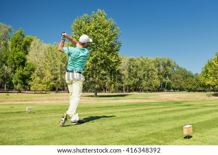 Golfer teeing off with iron club. Golf ball visible in the upper right corner. - stock photo