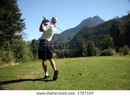 Golfer tees off on mountain course - stock photo