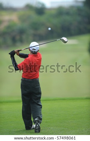 Golfer tees off on the Green - stock photo