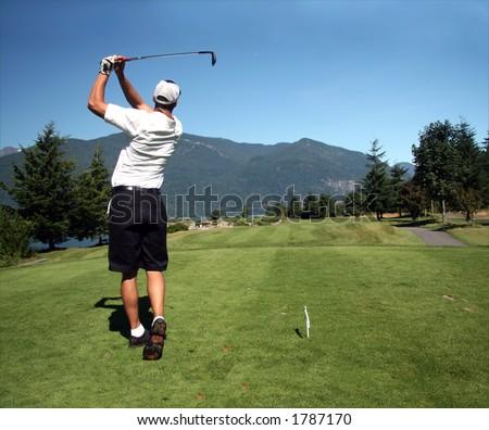 Golfer tees off towards ocean green - stock photo