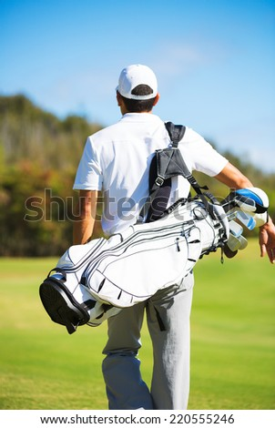 Golfer with Golf Bag Walking down the Course - stock photo