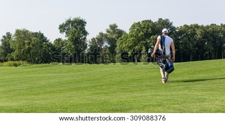 Golfer with golf bag walking down the course. Man going to spend his daytime playing golf isolated on green field background. - stock photo