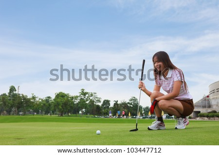 Golfer young woman lining up a putt on the green - stock photo