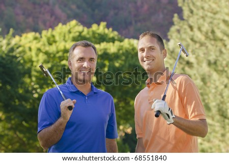 Golfers enjoying a day on the course - stock photo