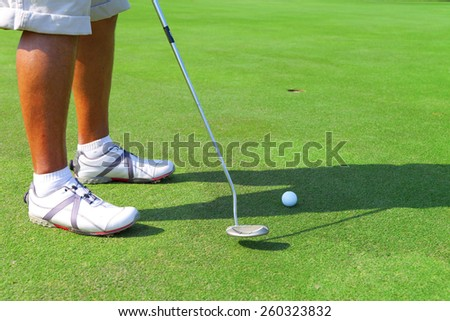 golfers feet with ball in front of the hole - stock photo