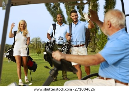 Golfers greeting on golf course, waving, smiling. - stock photo