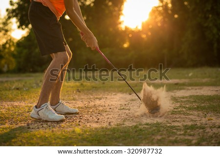 Golfers hit balls in the sand in the sunshine. - stock photo