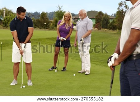 Golfers playing on the green, young an holing. - stock photo