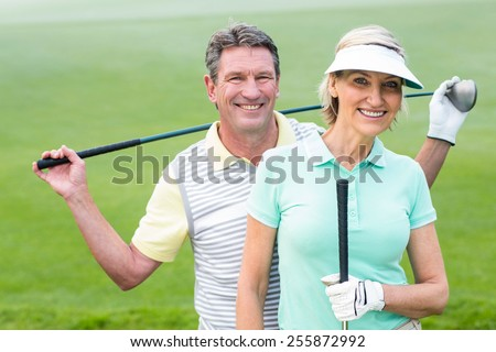 Golfing couple smiling at camera holding clubs on a foggy day at the golf course - stock photo