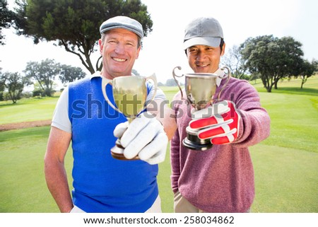 Golfing friends showing their cups at the golf course