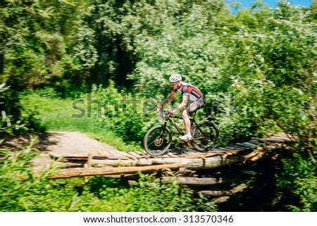 GOMEL, BELARUS - JUNE 7, 2015: Mountain Bike cyclist riding track at sunny day, healthy lifestyle active athlete doing sport. Blurred motion - stock photo