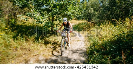 GOMEL, BELARUS - JUNE 7, 2015: Young woman mountain Bike cyclist riding track in forest at sunny day, healthy lifestyle active athlete doing sport - stock photo