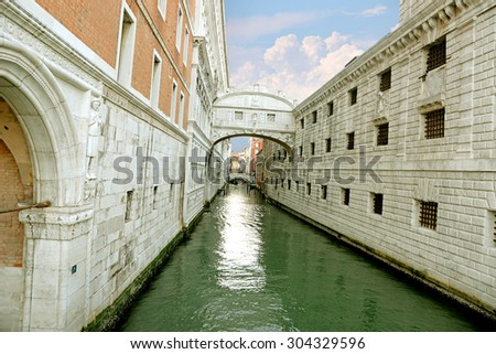 Gondola on small canal passing towards famous Bridge of Sighs (Ponte dei Sospiri) in Venice, Italy. - stock photo