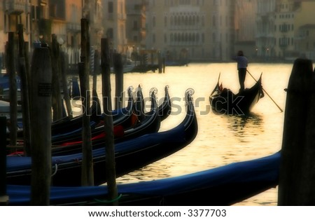 Gondola passing by gondolas parking on Grand Canal at sunset time in Venice, Italy. - stock photo
