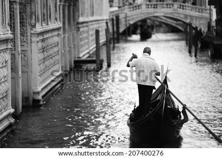 Gondola with gondolier on a channel in Venice, Italy  - stock photo