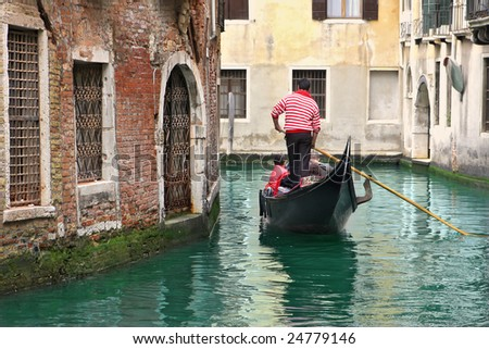 Gondola with tourists passing on narrow canal among old houses in Venice, Italy. - stock photo