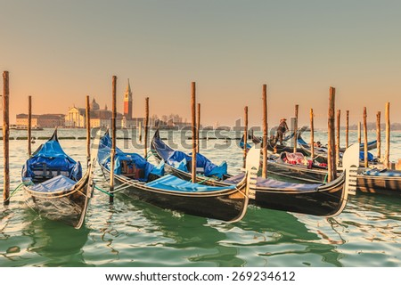 Gondolas docked to the poles on the Grand Canal in Venice. - stock photo