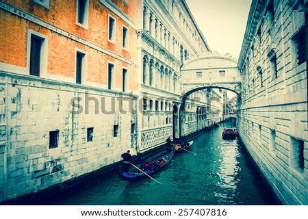 Gondolas floating on canal towards Bridge of Sighs (Ponte dei Sospiri). Venice, Italy. Perspective. Aged photo. - stock photo
