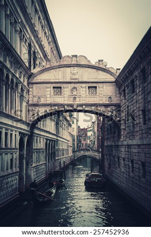 Gondolas floating on canal towards Bridge of Sighs (Ponte dei Sospiri). Venice, Italy. Perspective. Toned Gothic dark photo. - stock photo