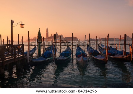 Gondolas in venice at sunset - San Giorgio maggiore on background - stock photo