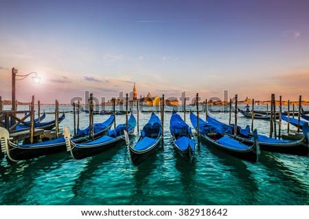 Gondolas in Venice - sunset with San Giorgio Maggiore church. San Marco, Venice, Italy. Intentional motion blur. - stock photo