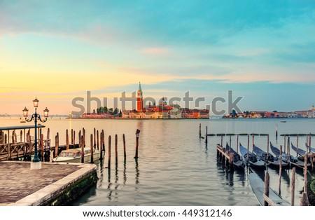 Gondolas moored by Saint Mark square with San Giorgio di Maggiore church in the background on a sunrise. Venice, Venezia, Italy, Europe. This image is toned.  - stock photo