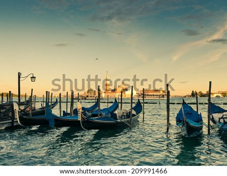 Gondolas moored by Saint Mark square with San Giorgio di Maggiore church in the background - Venice, Italy