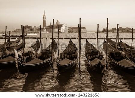 Gondolas moored by Saint Mark square with San Giorgio di Maggiore church in the background - Venice, Venezia, Italy, Europe, sepia image  - stock photo