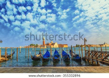 Gondolas moored by Saint Mark square with San Giorgio di Maggiore church in the background wirh clouds - Venice, Venezia, Italy - stock photo
