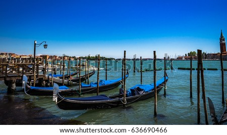 Gondolas moored by Saint Mark square with San Giorgio di Maggiore church on the background in Venice, Italy at sunny day.