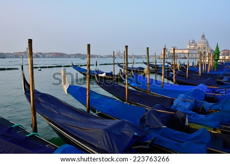 Gondolas moored by Saint Mark square with Santa Maria della Salute church in the background at sunrise - Venice, Italy, Europe