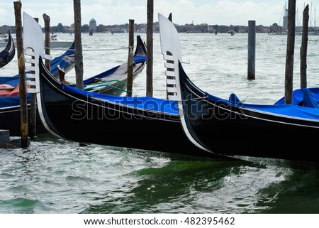 Gondolas moored in landing passengers on the Grand canal in the Adriatic Sea near Saint Mark's square. Venice. Italy.