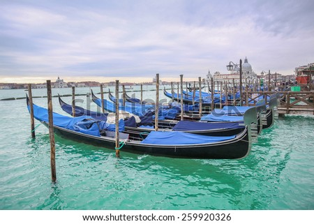 Gondolas moored in the water with a view of Santa Maria della Salute church in Venice, Italy. - stock photo